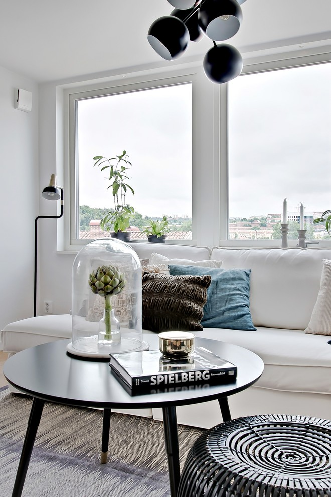 Inspiration for a scandinavian open concept and formal light wood floor living room remodel in Gothenburg with white walls and no tv