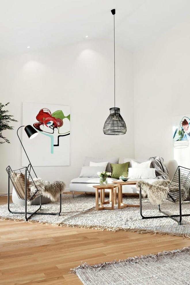 Living room - scandinavian open concept medium tone wood floor and brown floor living room idea in Stockholm with white walls