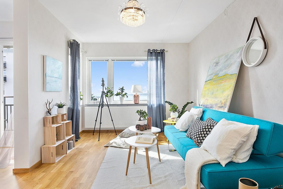 Inspiration for a mid-sized scandinavian open concept and formal medium tone wood floor living room remodel in Gothenburg with no tv, gray walls and no fireplace