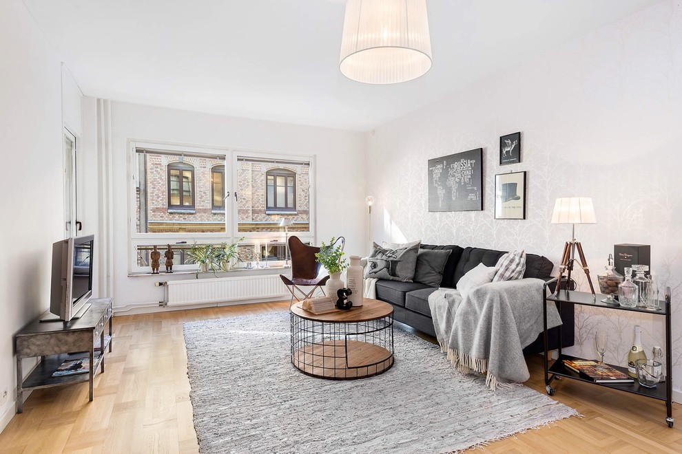 Example of a mid-sized danish medium tone wood floor living room design in Gothenburg with white walls and a tv stand