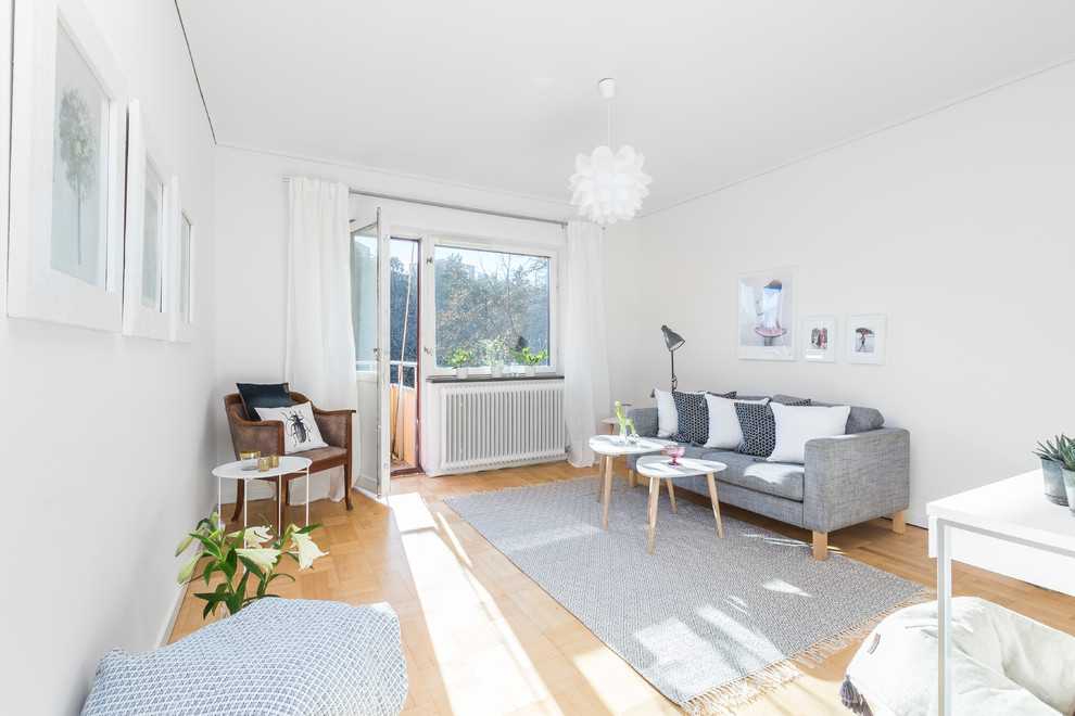 Example of a mid-sized danish formal and enclosed medium tone wood floor living room design in Stockholm with white walls, no fireplace and no tv