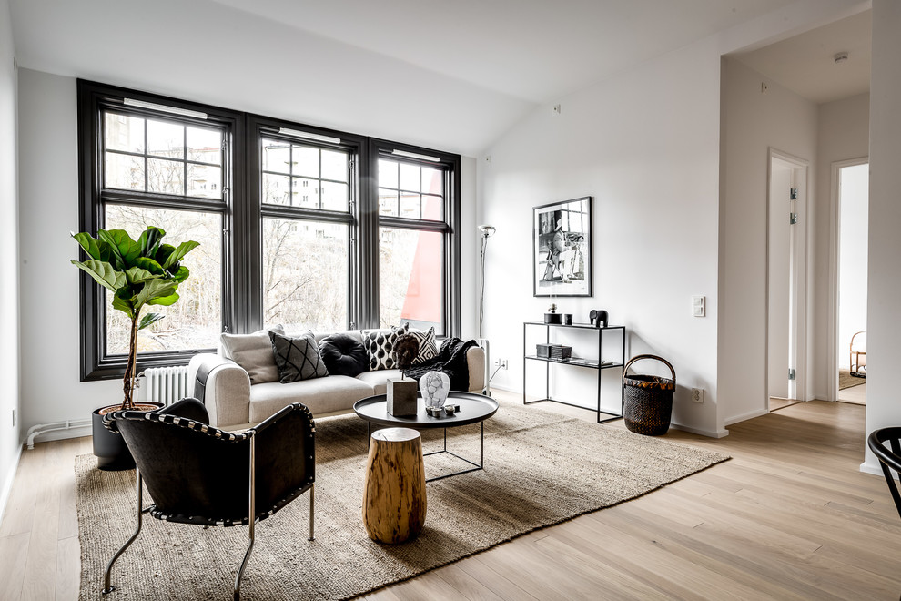 Example of a large trendy formal and enclosed light wood floor and brown floor living room design in Stockholm with white walls, no fireplace and no tv