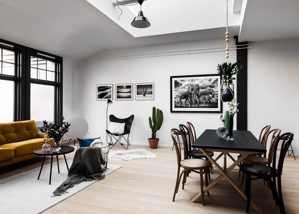 Example of a danish open concept light wood floor and beige floor living room design in Stockholm with white walls