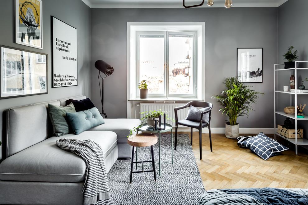 Living room - scandinavian enclosed light wood floor and gray floor living room idea in Stockholm with gray walls