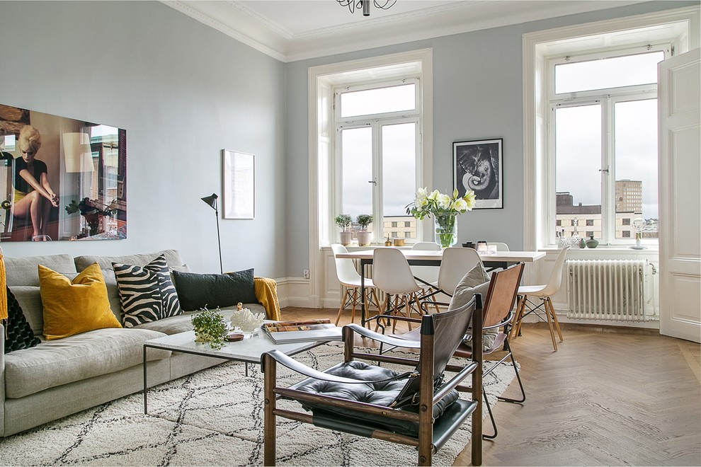 Example of a large danish formal and enclosed medium tone wood floor living room design in Stockholm with gray walls, no fireplace and no tv