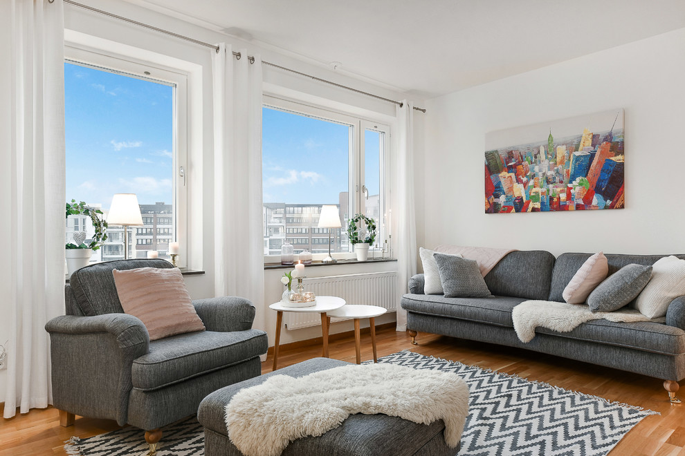 Example of a mid-sized danish formal and open concept medium tone wood floor living room design in Stockholm with white walls
