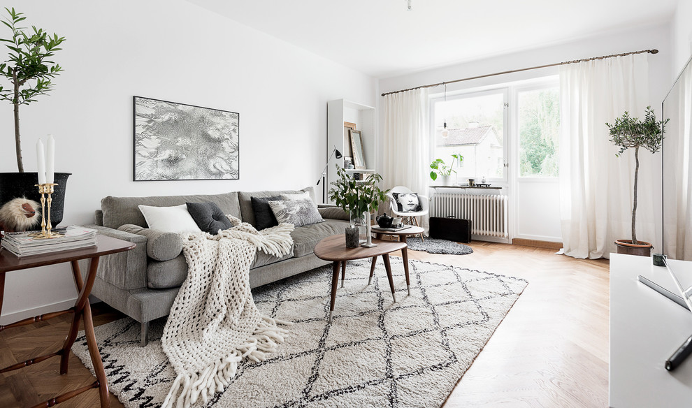 Inspiration for a mid-sized scandinavian open concept medium tone wood floor and brown floor living room remodel in Gothenburg with white walls and a tv stand