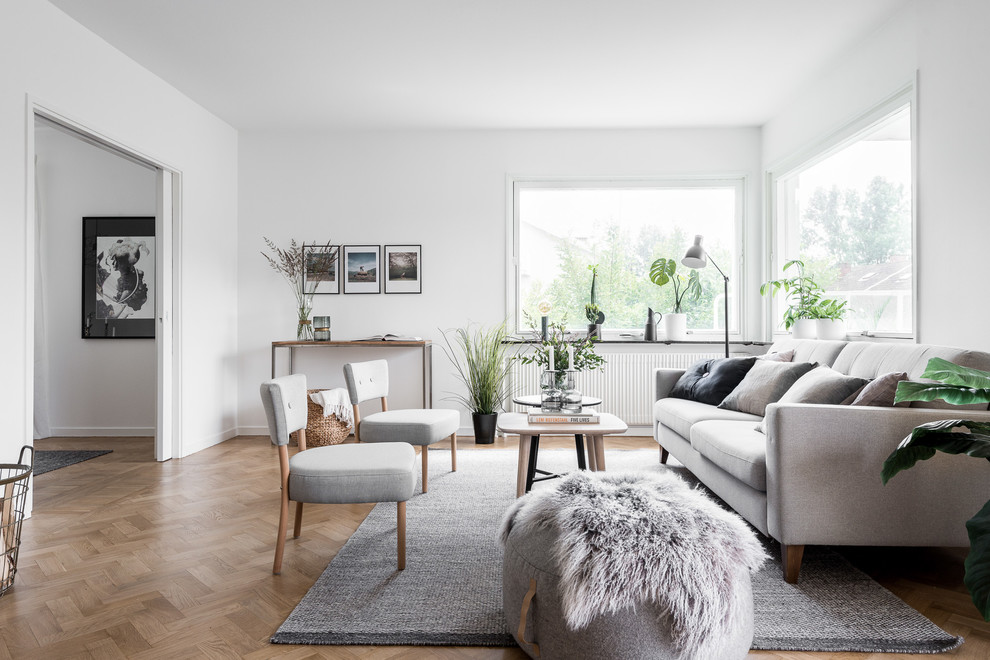 Inspiration for a mid-sized scandinavian enclosed and formal medium tone wood floor living room remodel in Gothenburg with white walls
