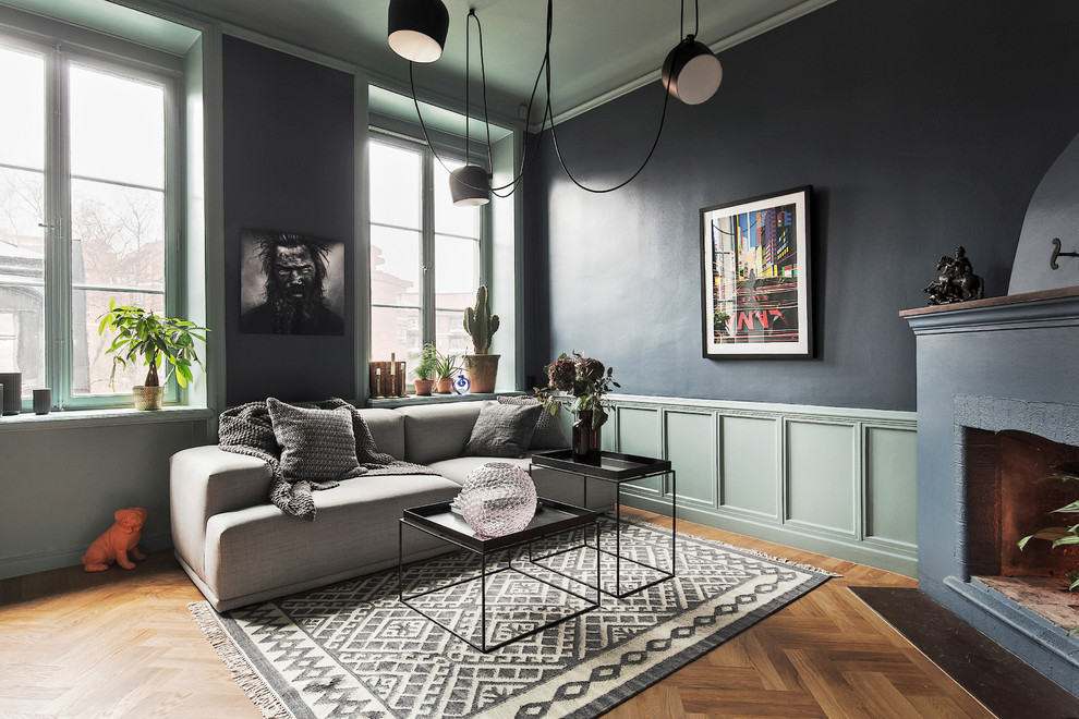 Mid-sized danish formal and open concept medium tone wood floor living room photo in Stockholm with blue walls, a corner fireplace and no tv