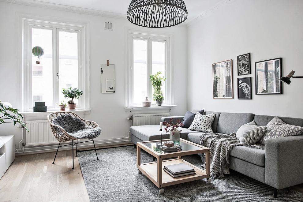 Living room - scandinavian enclosed light wood floor and beige floor living room idea in Gothenburg with white walls