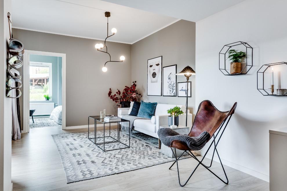Mid-sized danish open concept light wood floor and gray floor living room photo in Gothenburg with beige walls and no tv