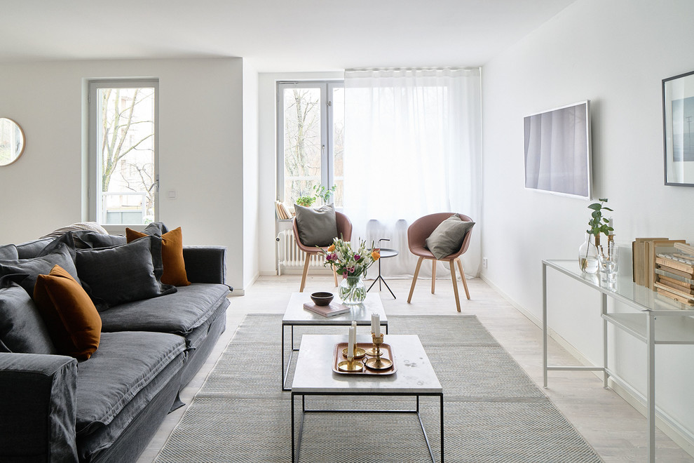 Mid-sized danish open concept light wood floor living room photo in Stockholm with white walls, no fireplace and a wall-mounted tv