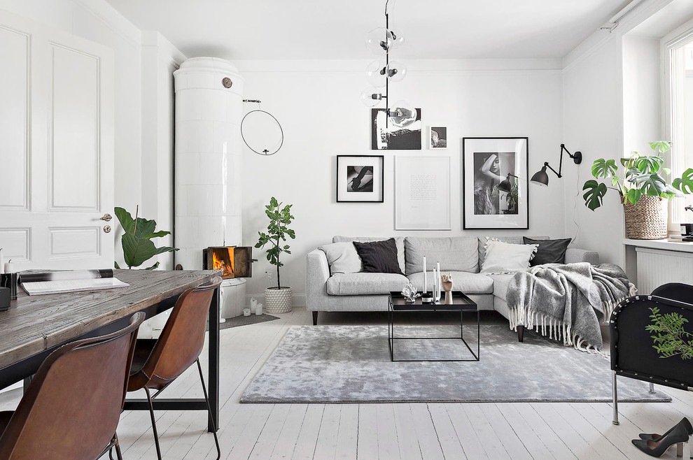 Inspiration for a scandinavian painted wood floor and white floor living room remodel in Stockholm with white walls, a corner fireplace and a tile fireplace