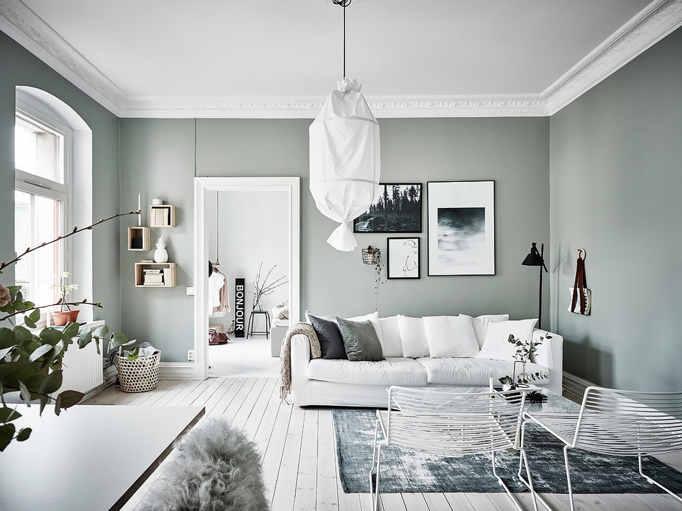 Example of a danish enclosed light wood floor and white floor living room design in Gothenburg with green walls, no fireplace and no tv