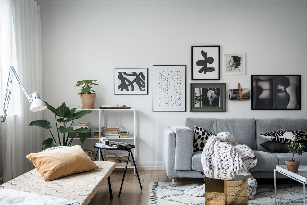 Inspiration for a mid-sized scandinavian enclosed light wood floor and beige floor living room remodel in Gothenburg with white walls and no fireplace