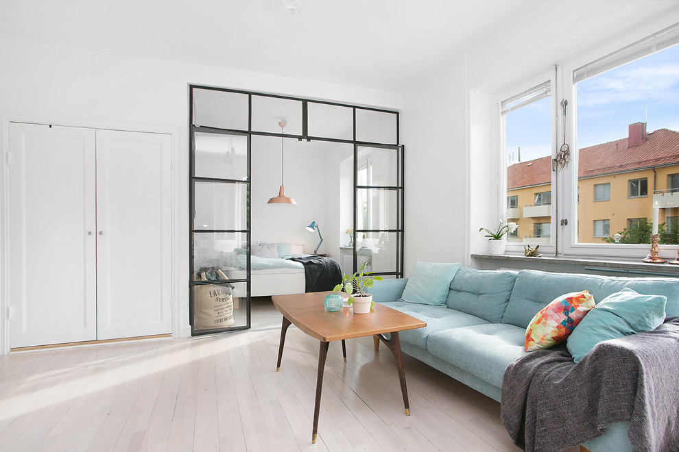 Example of a mid-sized danish formal and open concept light wood floor living room design in Stockholm with white walls and no tv