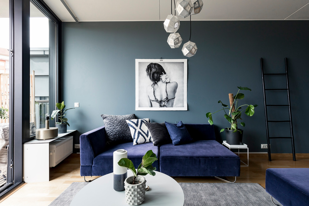 Mid-sized trendy enclosed medium tone wood floor living room photo in Stockholm with blue walls