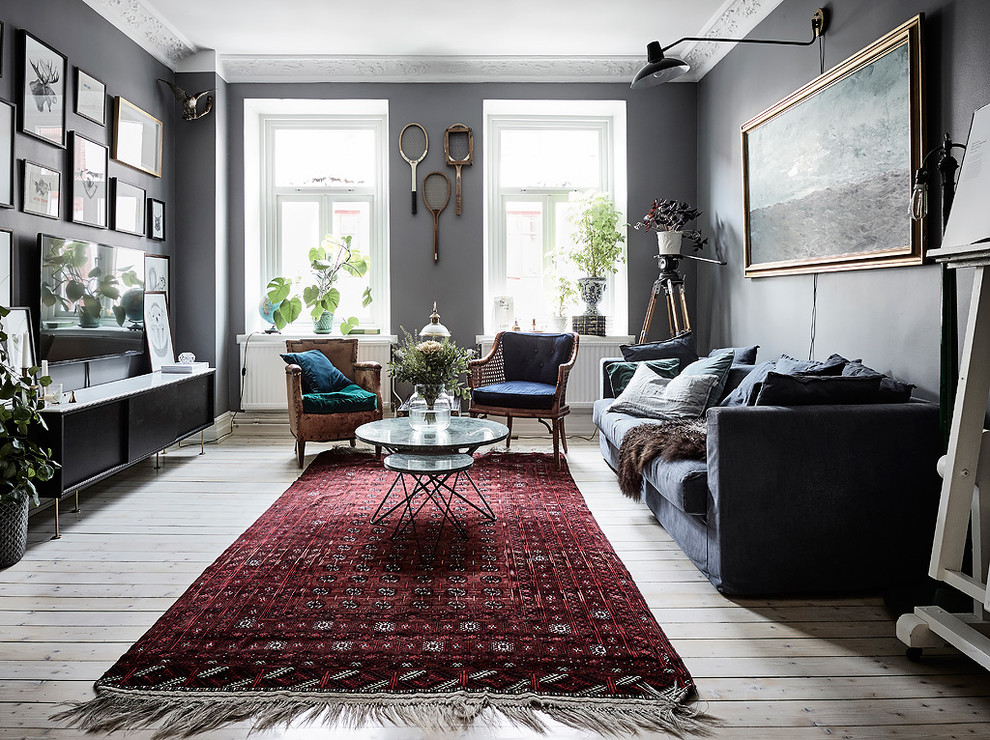Example of a danish enclosed light wood floor and beige floor living room design in Gothenburg with gray walls and a wall-mounted tv