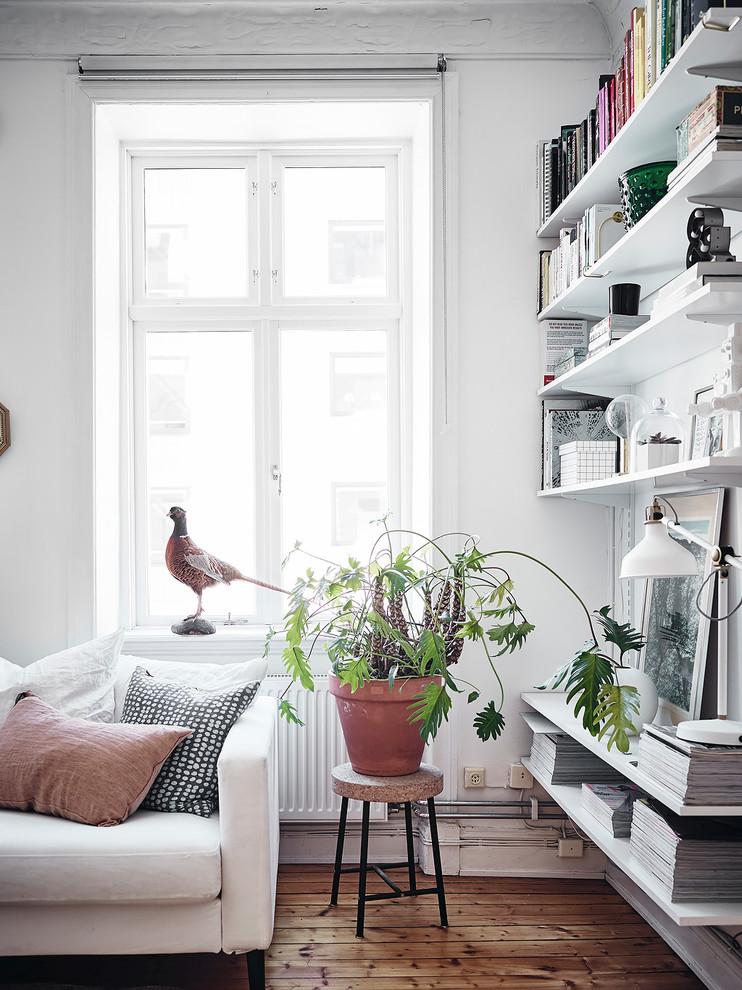 Idéer för att renovera ett skandinaviskt vardagsrum, med vita väggar, mellanmörkt trägolv och brunt golv