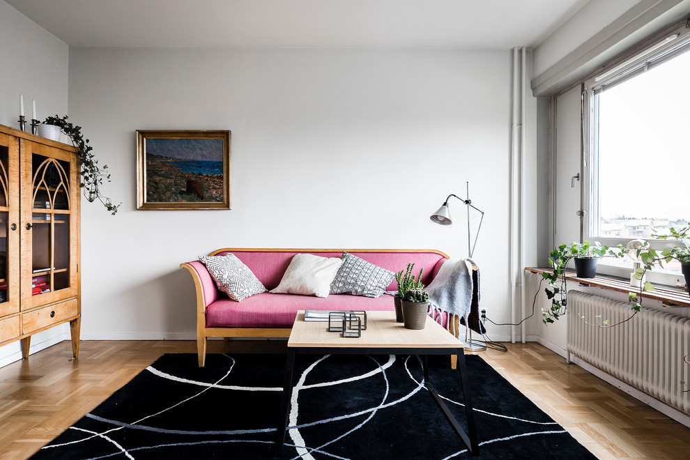 Example of a mid-sized danish enclosed light wood floor and beige floor living room design in Stockholm with white walls