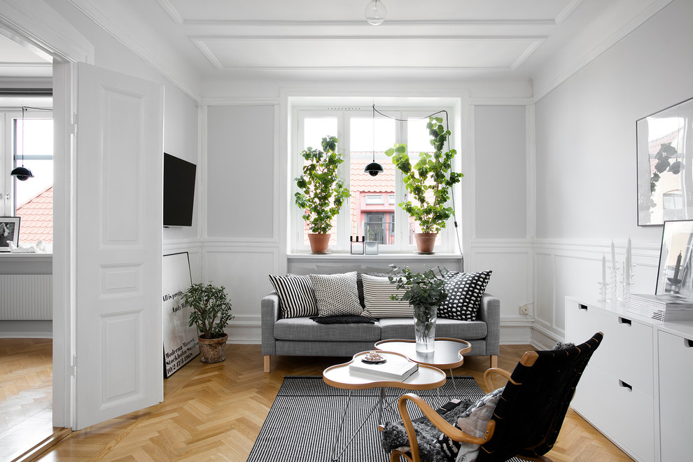 Living room - scandinavian medium tone wood floor and brown floor living room idea in Malmo with gray walls