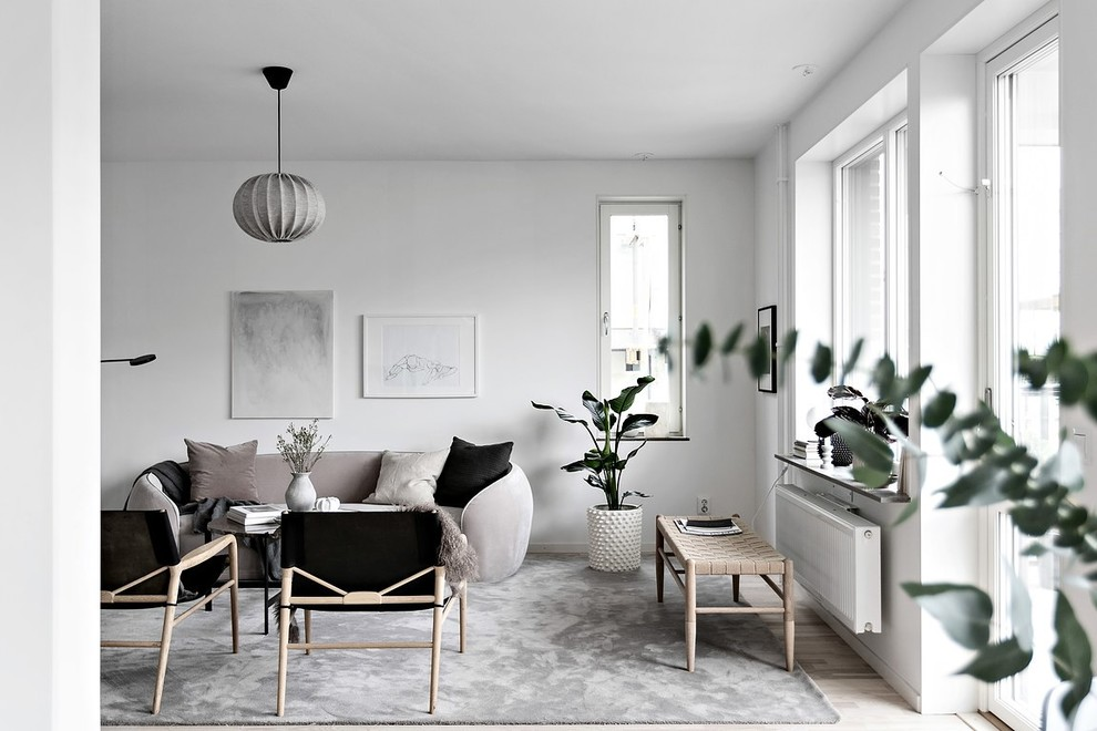 Example of a danish light wood floor and beige floor living room design in Stockholm with white walls