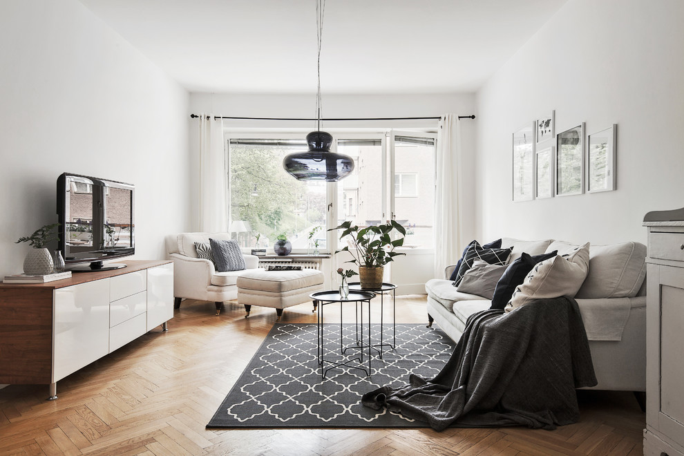 Living room - mid-sized scandinavian formal light wood floor living room idea in Stockholm with white walls and a tv stand