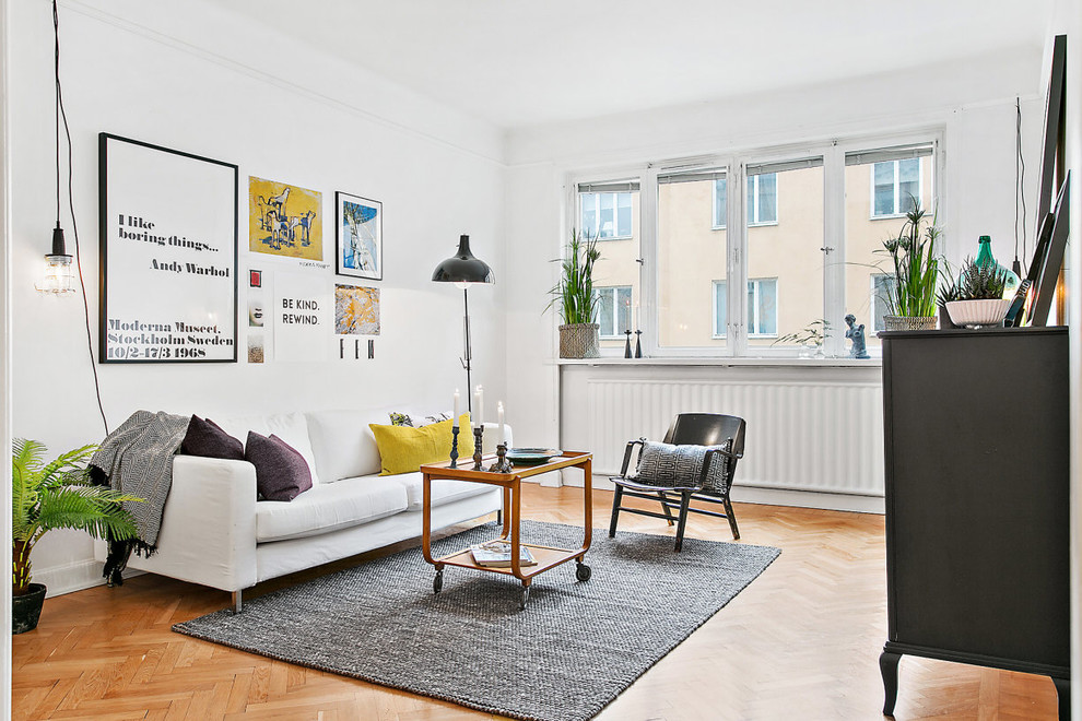 Living room - mid-sized scandinavian formal and open concept medium tone wood floor living room idea in Stockholm with white walls, no fireplace and no tv