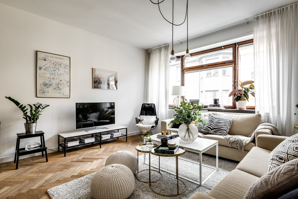 Danish formal medium tone wood floor and brown floor living room photo in Stockholm with white walls and a tv stand