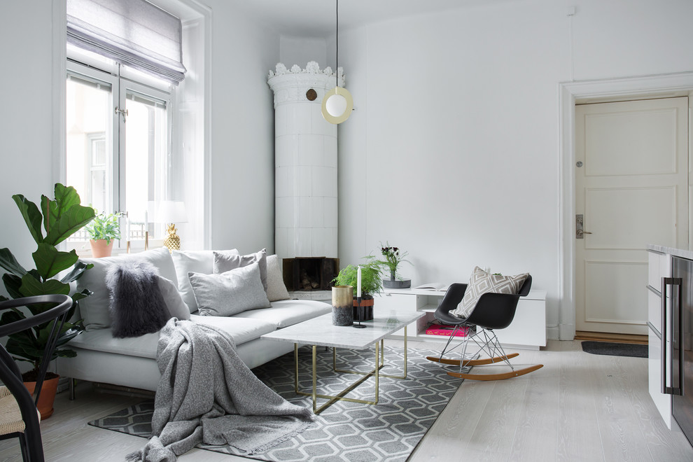 Inspiration for a scandinavian enclosed laminate floor and gray floor living room remodel in Stockholm with white walls, a wood stove and a metal fireplace