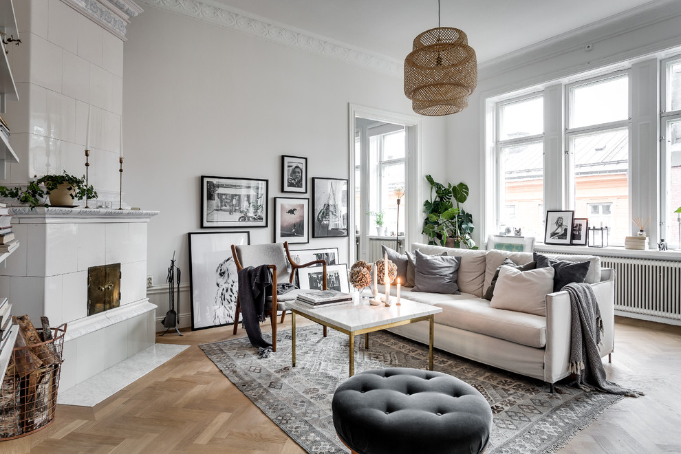 Inspiration for a mid-sized scandinavian formal and open concept medium tone wood floor living room remodel in Stockholm with white walls, a corner fireplace and a tile fireplace
