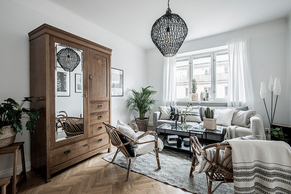 Inspiration for a mid-sized scandinavian enclosed medium tone wood floor and brown floor living room remodel in Stockholm with white walls and no fireplace