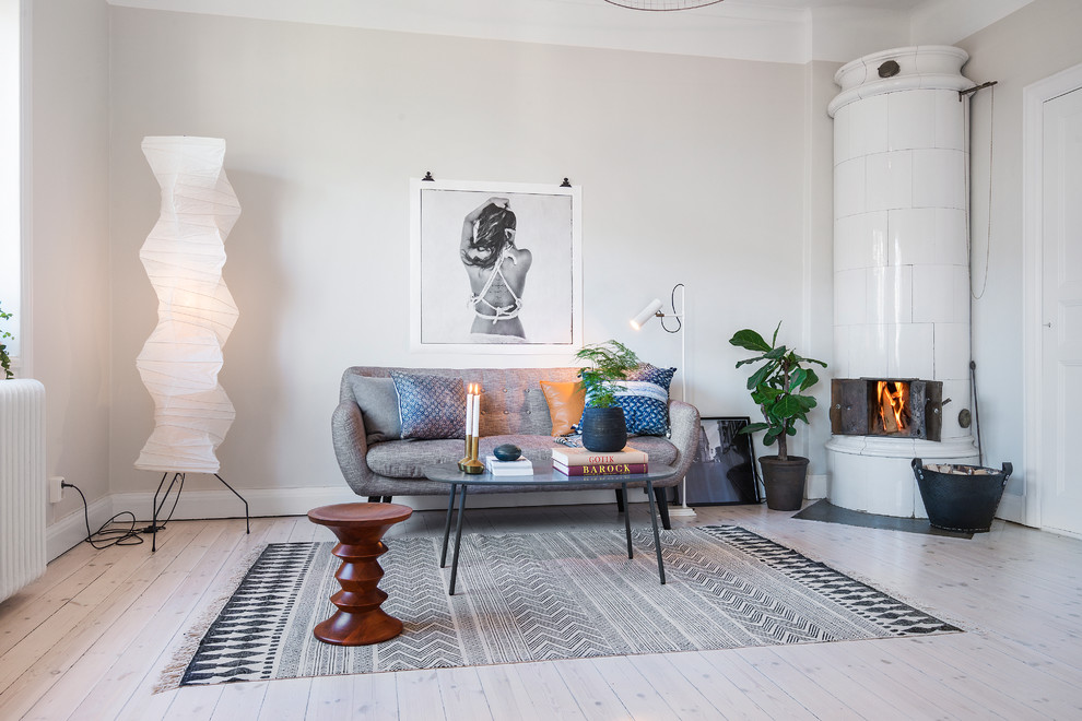 Living room - large scandinavian formal and open concept light wood floor living room idea in Stockholm with beige walls, a wood stove and no tv