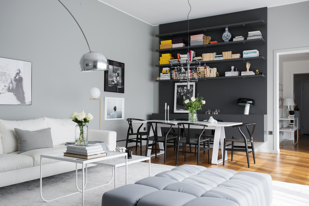Mid-sized minimalist open concept medium tone wood floor living room photo in Stockholm with black walls and no fireplace