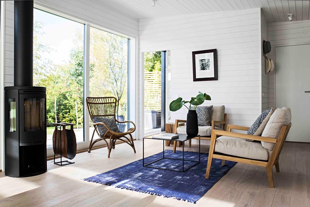 Inspiration för ett mellanstort nordiskt allrum med öppen planlösning, med vita väggar, ljust trägolv, en standard öppen spis och en spiselkrans i metall
