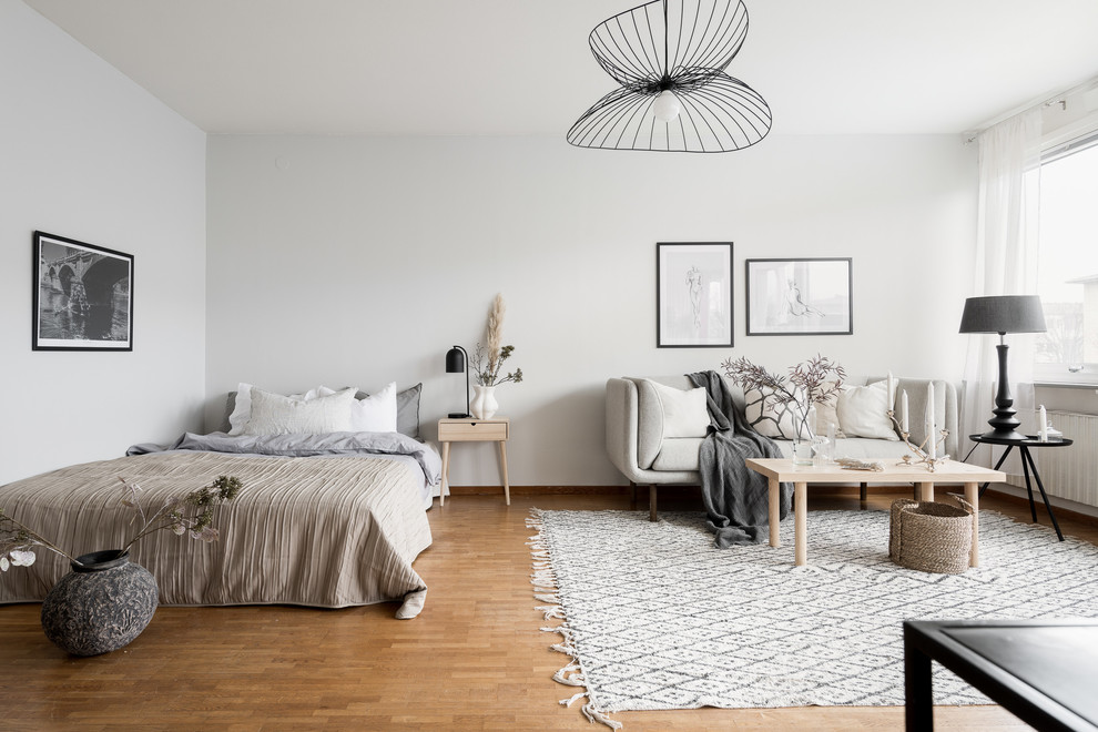 This is an example of a small scandi open plan living room in Gothenburg with white walls and medium hardwood flooring.
