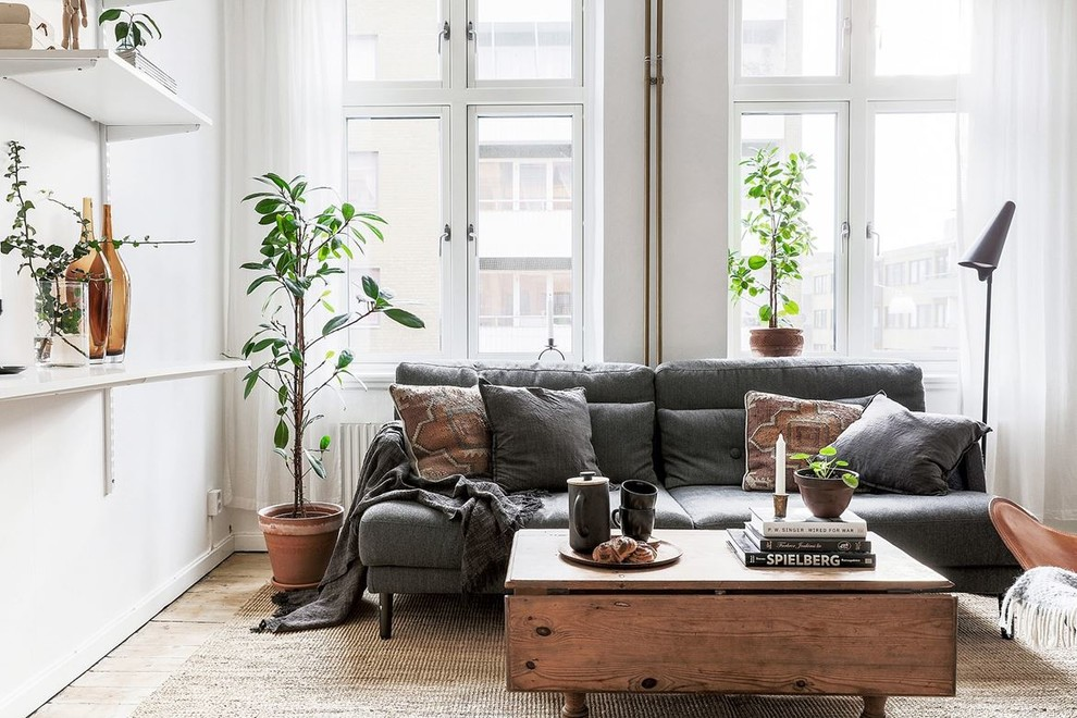 Mid-sized danish enclosed light wood floor and beige floor living room photo in Malmo with white walls