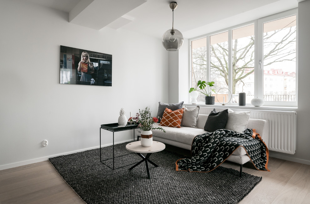 Living room - small scandinavian enclosed laminate floor and beige floor living room idea in Stockholm with white walls and a wall-mounted tv