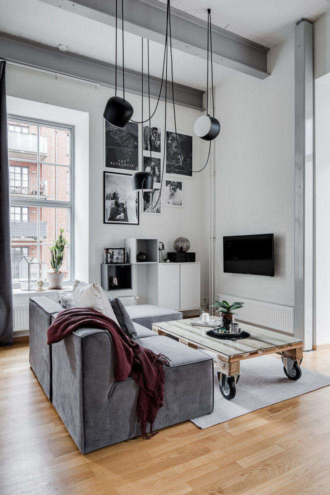 Living room - mid-sized industrial medium tone wood floor and brown floor living room idea in Gothenburg with white walls, no fireplace and a wall-mounted tv