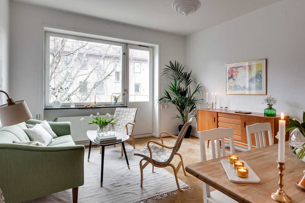 Example of a mid-sized danish formal and enclosed light wood floor living room design in Stockholm with white walls, no fireplace and no tv