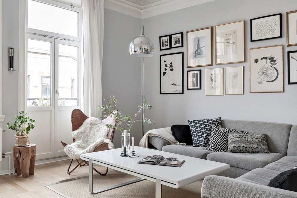 Danish formal and enclosed light wood floor and beige floor living room photo in Malmo with gray walls