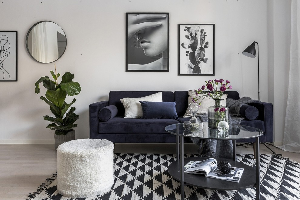 Example of a mid-sized danish enclosed light wood floor and gray floor living room design in Stockholm with white walls