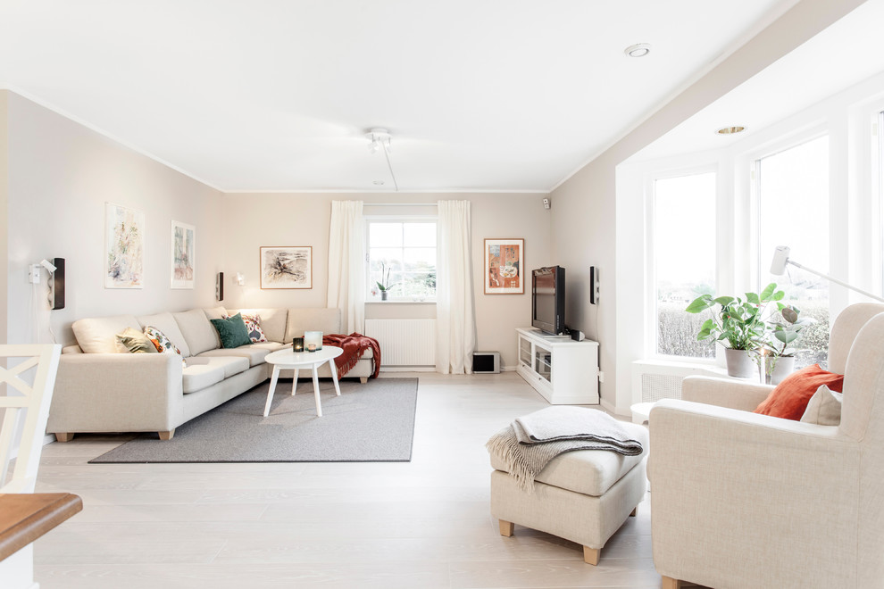 Inspiration for a large scandinavian open concept light wood floor living room remodel in Gothenburg with no fireplace, a tv stand and beige walls