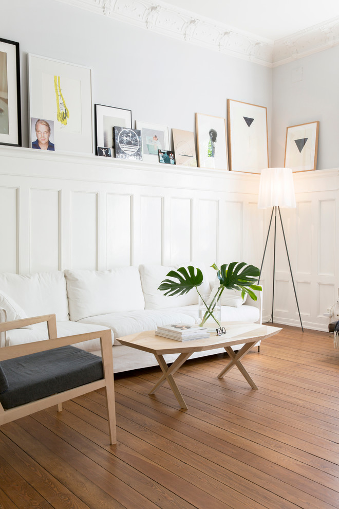 Mid-sized danish open concept and formal light wood floor living room photo in Gothenburg with white walls and no tv