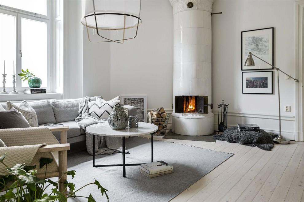 Idee per un soggiorno scandinavo di medie dimensioni e aperto con pareti bianche, parquet chiaro, stufa a legna, cornice del camino piastrellata, nessuna TV e sala formale