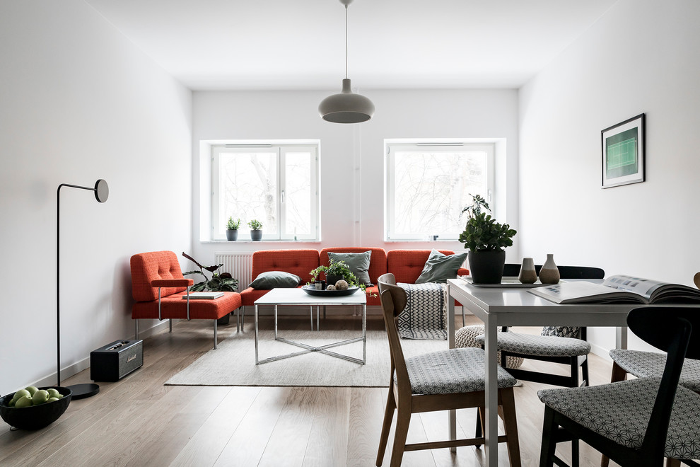 Example of a small danish open concept light wood floor and beige floor living room design in Stockholm with white walls and no fireplace
