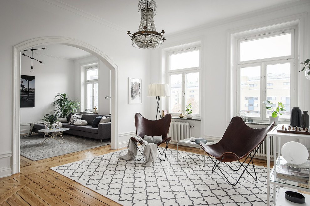 Large danish formal and open concept medium tone wood floor and brown floor living room photo in Stockholm with white walls and no fireplace