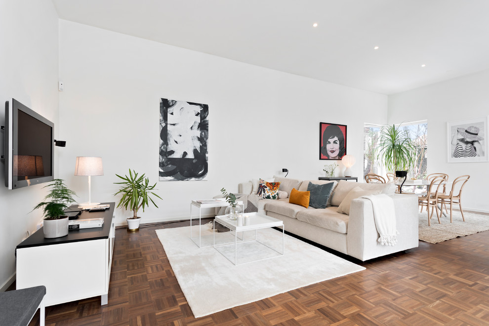 Mid-sized danish open concept brown floor and medium tone wood floor living room photo in Stockholm with white walls, no fireplace and a wall-mounted tv