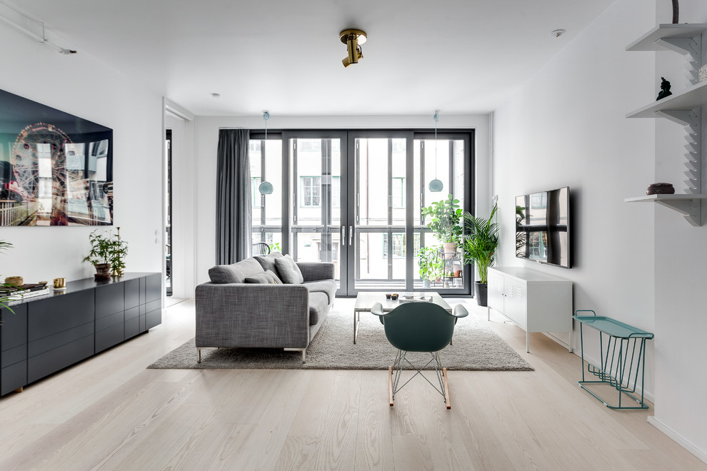 Living room - mid-sized scandinavian open concept and formal light wood floor living room idea in Stockholm with white walls and a wall-mounted tv