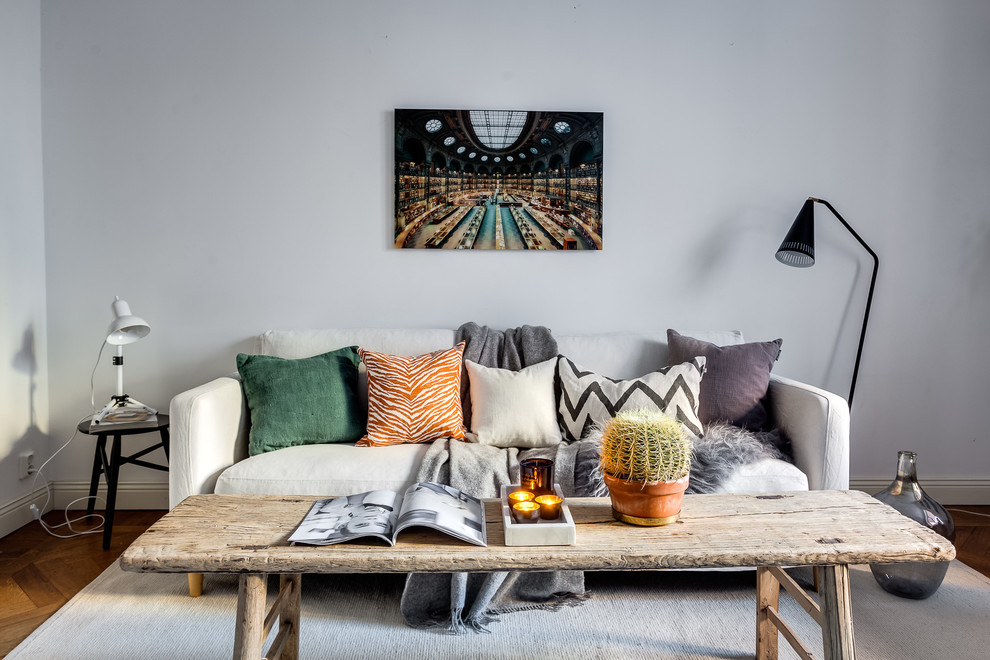 Inspiration for a mid-sized scandinavian medium tone wood floor living room remodel in Stockholm with gray walls, no fireplace and no tv
